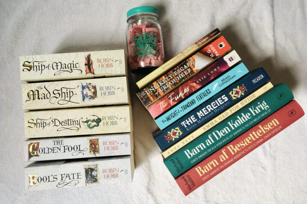 To stakke af bøger på en hvid baggrund. Mellen stakkene ligger en glaskrukke med lyserøde papirstykker. Stakken til venstre består af fem tykke bøger af forfatteren Robin Hobb. Stakken til højre er en blandet stak af blandt andet historisk bøger, erindringer og YA mysterier.