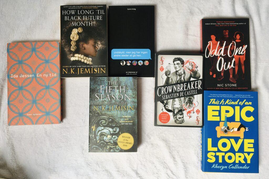 Syv bøger på en hvis baggrund. bøgerne ligger spredt i et vilkårligt mønster.