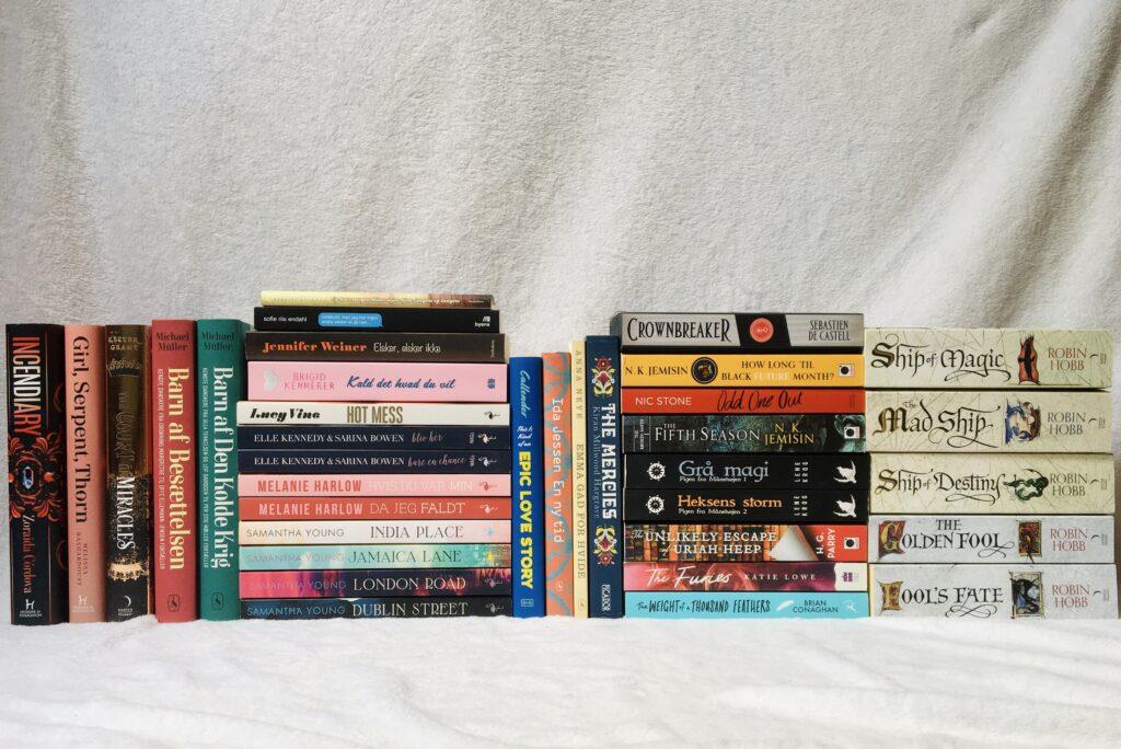 36 bøger på en hvid baggrund. Bøgerne er stakket op i nogenlunde samme højde og er lidt blandet.